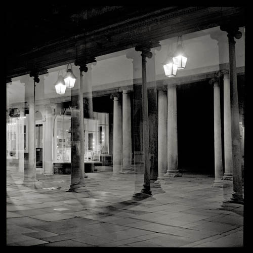 night picture double expsure of ionic columns in bath with illuminated lamps bath england united kingdom