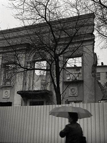 black and white picture using a 1938 zeiss ikonta 520 of the destruction of a turn of the century building in kiev near arsenal factory for making a new modern building in the rain with a woman in front holding an umbrella